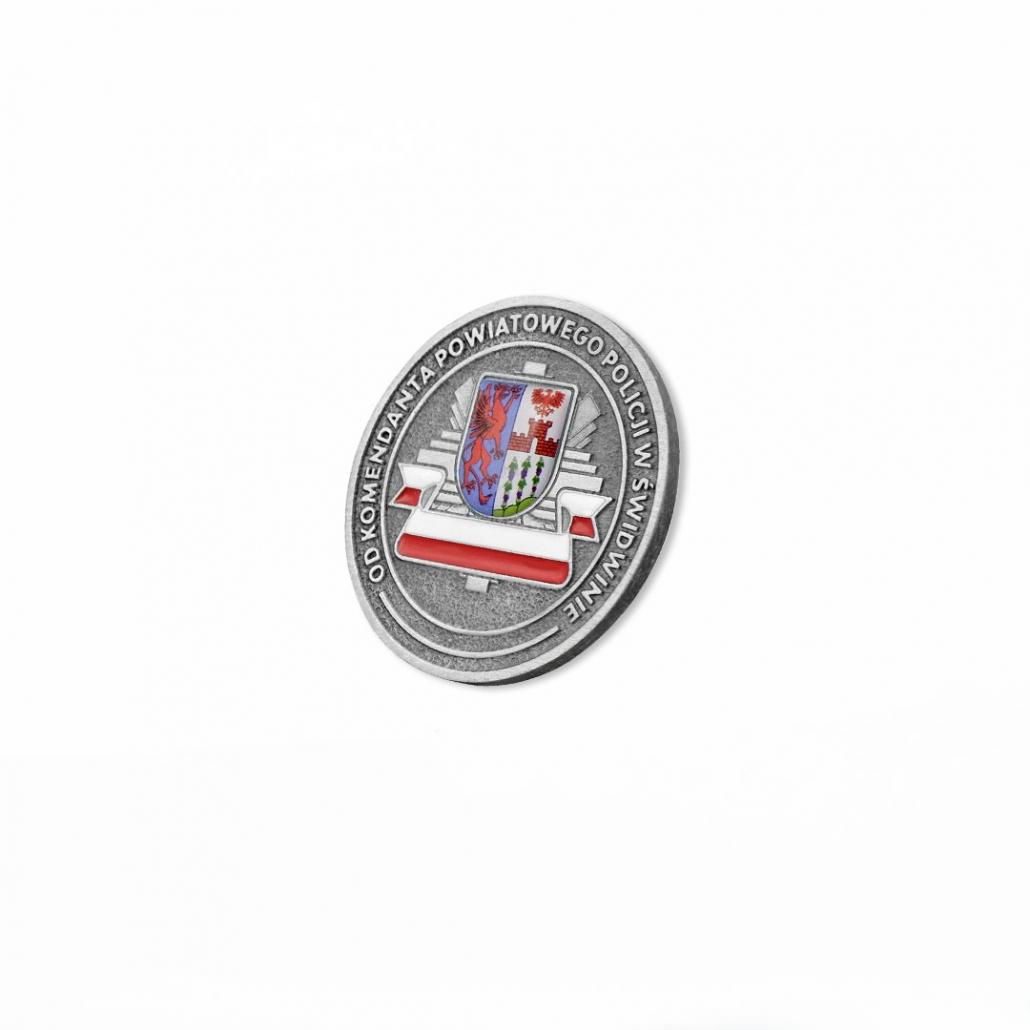 Eine gegossene Münze mit einem 3D-Einkleber, die einen Stadtwappen mit dem Polizeiabzeichen verbindet